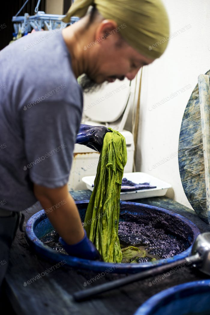 Japanese man wearing bandana standing in a textile plant dye workshop, dyeing piece of green fabric.