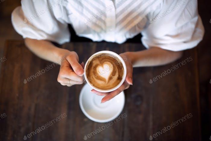 Vista superior de la mujer irreconocible sentada en el interior en la cafetería, sosteniendo el café