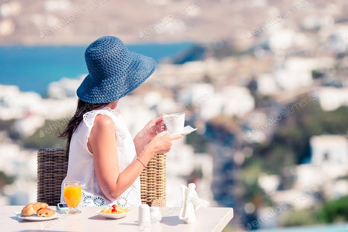 Woman having breakfast at outdoor cafe with amazing view on Mykonos town