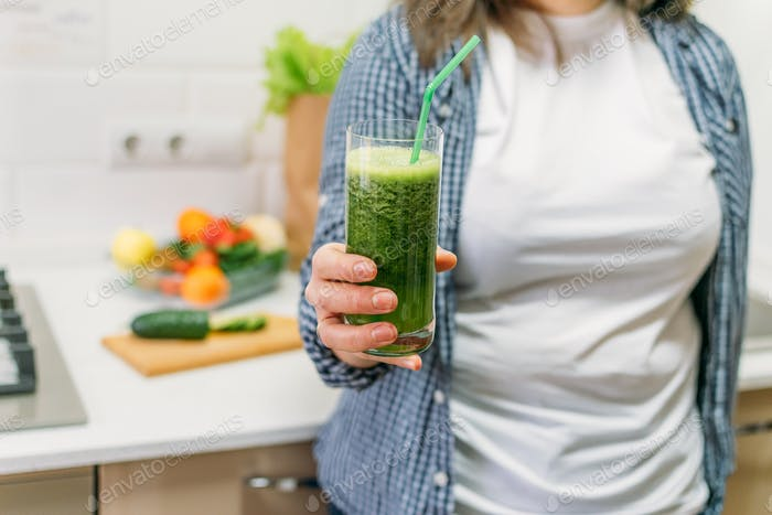 Green Smoothies for Weight Loss. Plus size woman holding in hand glass with slimming Green Smoothie