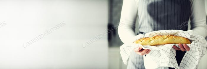 Woman hands holding freshly baked bread. French baguette, bakery concept, homemade food, healthy