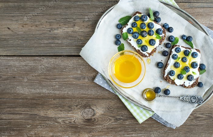 Healthy breakfast set with ricotta, fresh blueberries and honey