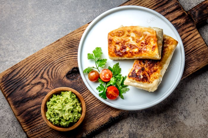 Mexican chimichanga on white plate served with guacamole sauce.