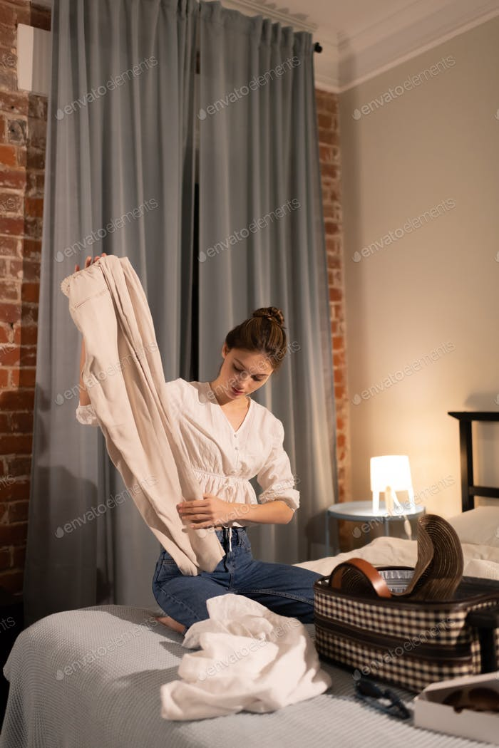Young lady packing suitcase for trip