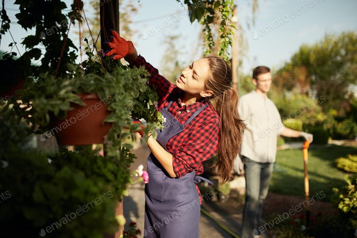 Beautiful girl gardener take care of the plants in the pot on the veranda while guy digs the ground