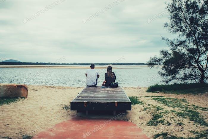 Junges Paar sitzen zusammen auf einer Bank und Blick auf den Fluss. Rückansicht