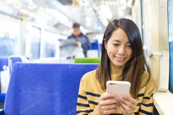 Женщина пользуется мобильным телефоном на поезде