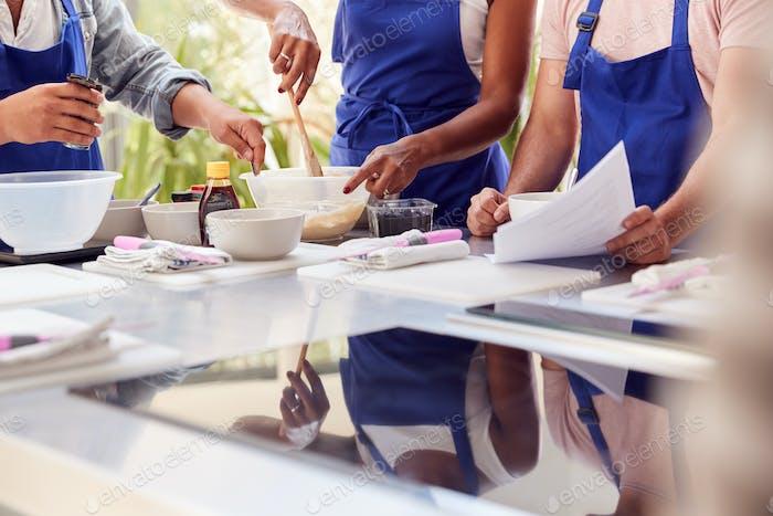 Cerca De Hombres Y Mujeres Adultos Estudiantes Mirando A Receta En La Clase De Cocina En Cocina