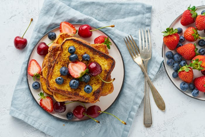 French toasts with berries, brioche breakfast, white background top view