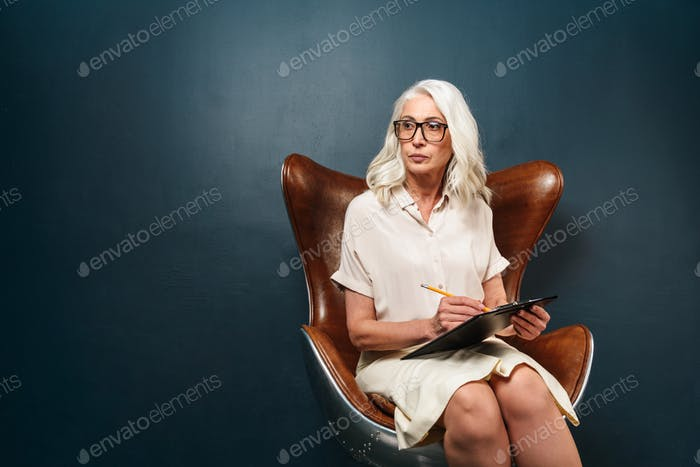 Serious mature old woman holding clipboard with documents writing notes.