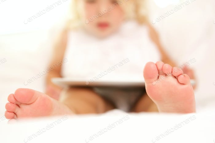 Little girl on bed with digital tablet
