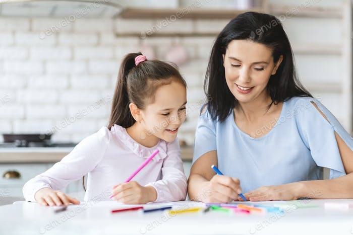 Cute little girl drawing together with her mom in kitchen