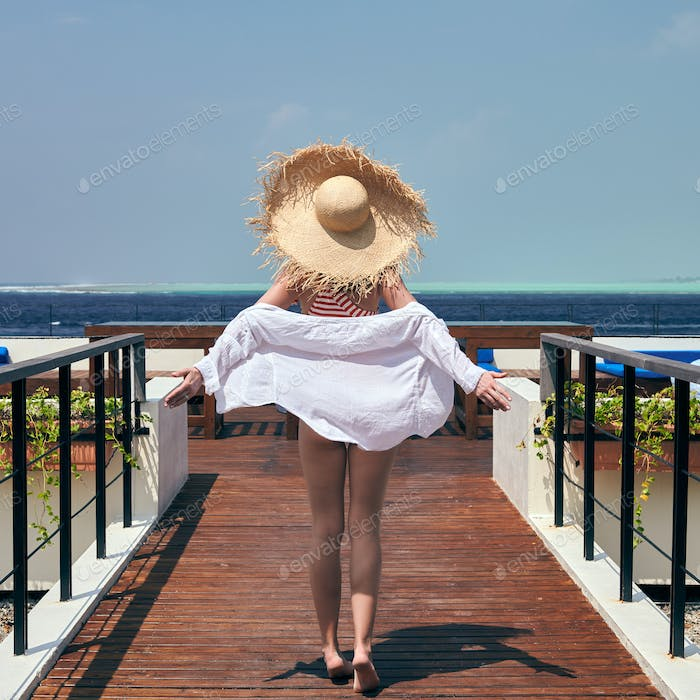 Woman in striped swimsuit on beach patio