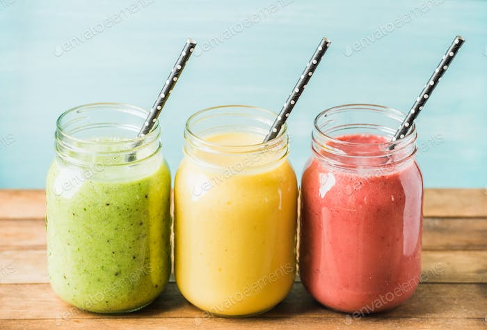 Three jars of fresh fruit smoothies with various colors and tastes. Green, yellow, red.