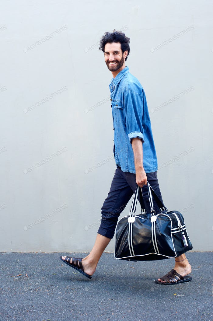 Happy modern man walking and holding travel bag