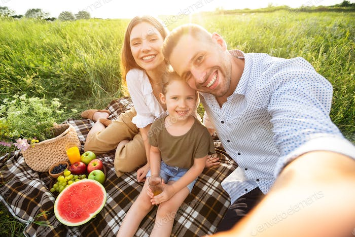 Happy loving family taking selfie in the countryside