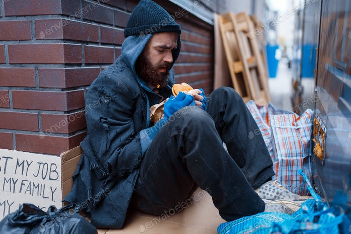 Bearded beggar eats burger on city street