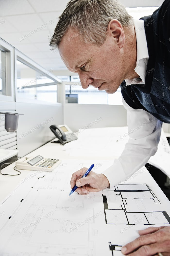 A caucasian businessman working on plans for an office layout.