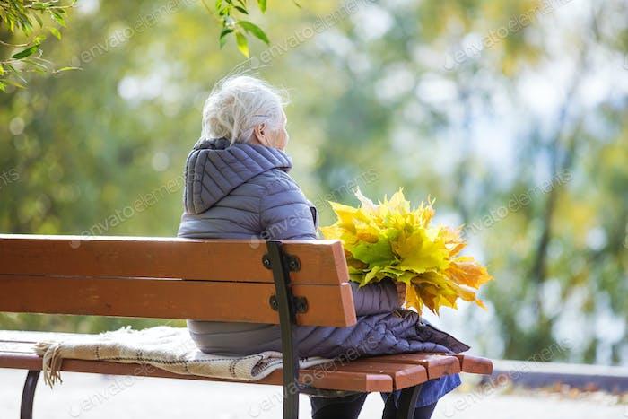 Senior woman sitting on bench in park