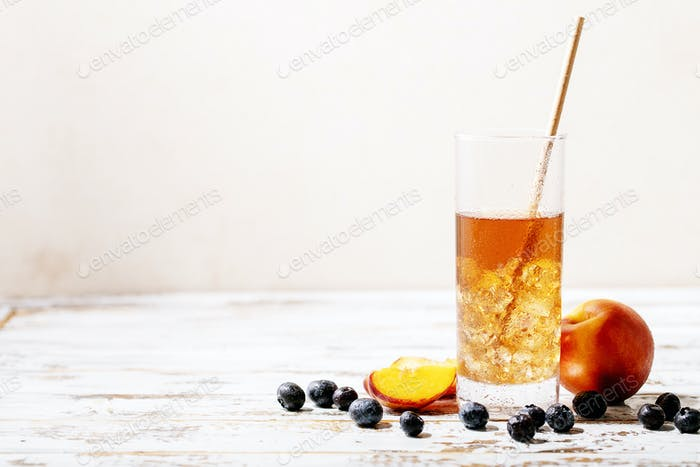 Cup of peach ice tea served with fresh peach