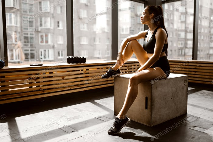 Charming slander girl dressed in black sports top and shorts is sitting on a wooden box in the