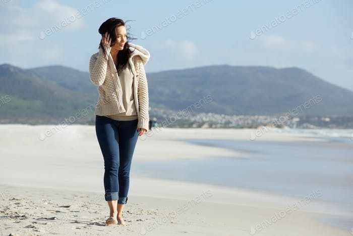 Attractive young lady walking on the sea shore