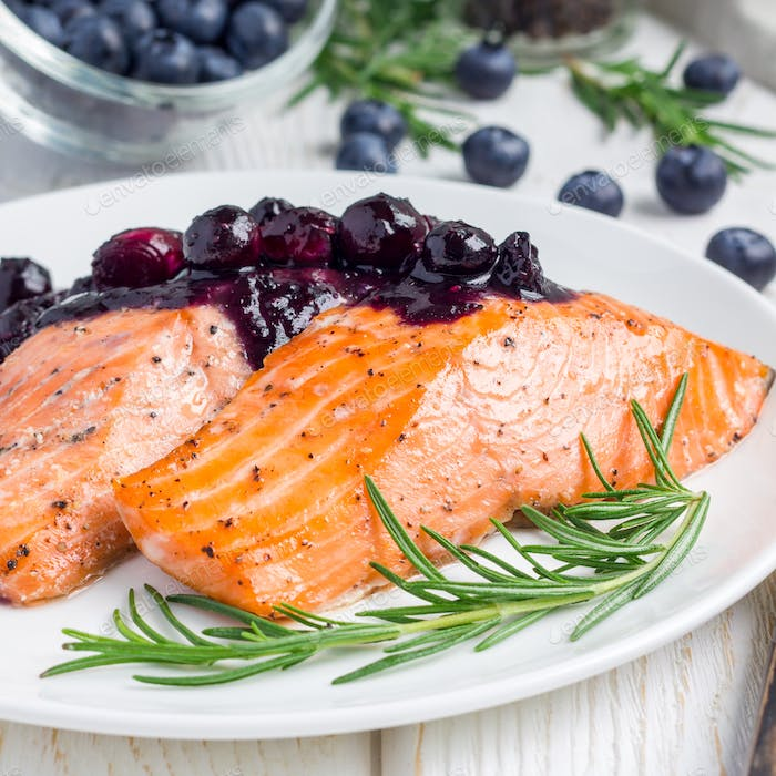 Baked salmon fillet with blueberry and rosmarin sauce on white plate, square