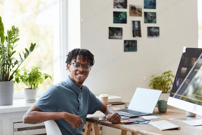 Kreativer afroamerikanischer Mann posiert am Schreibtisch im Büro