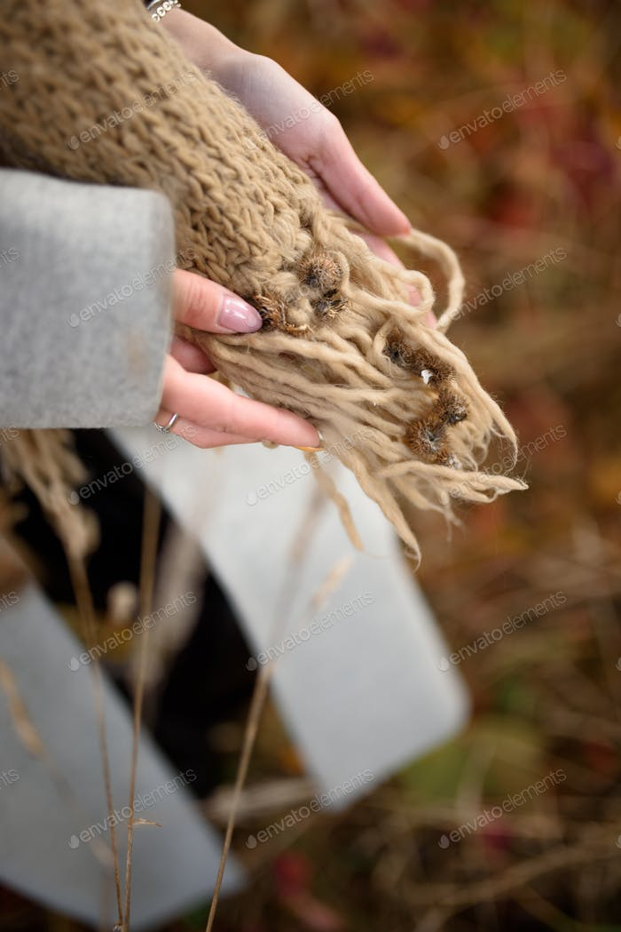 The girl holds in her hands a scarf full of burrs.