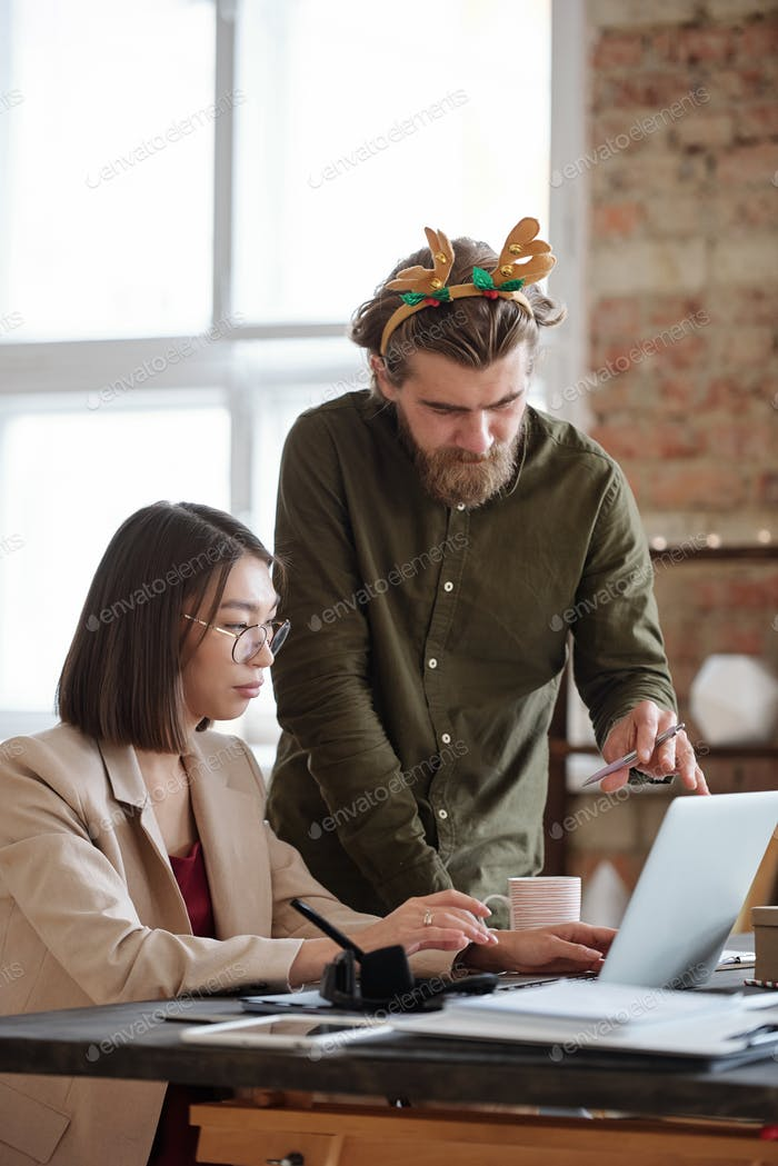 Young bearded businessman with xmas headwear helping colleague with presentation
