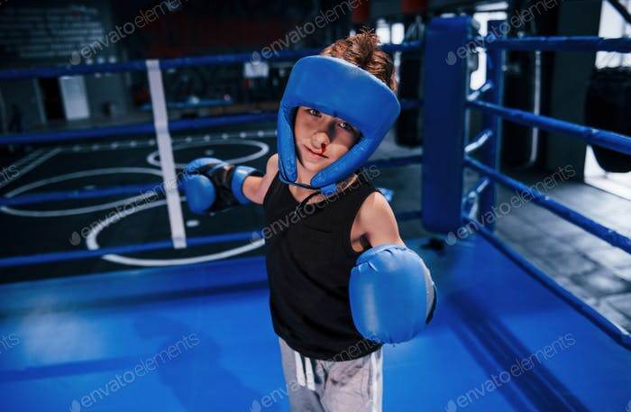 Little boy in protective wear and with nose bleed training in the boxing ring