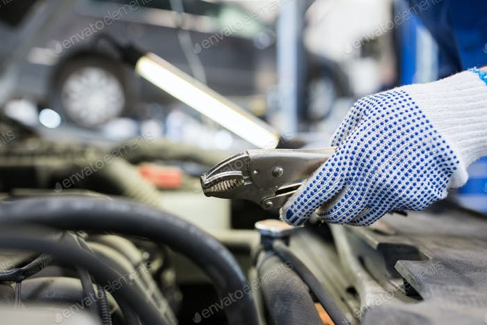mechanic man with pliers repairing car at workshop