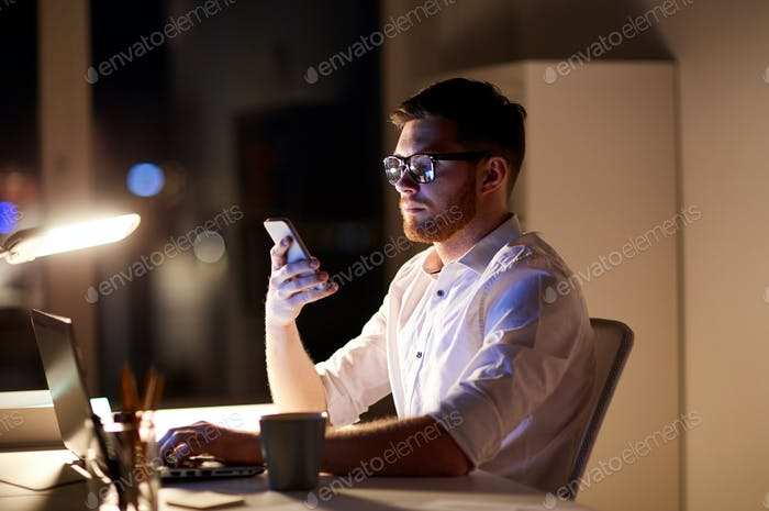 businessman texting on smartphone at night office