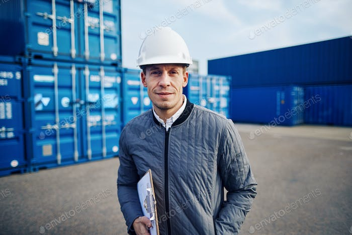 Smiling dock foreman standing in a commercial shipping yard