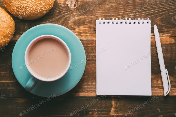 Notebook with a pen on the table next to cacao
