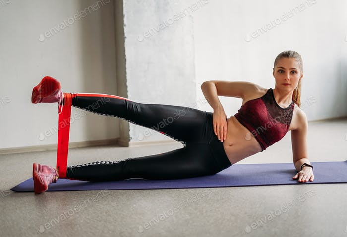 Young woman sport wear fitness girl model doing stretching with elastic band