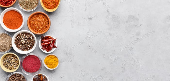 Spices and condiments in bowls on grey background