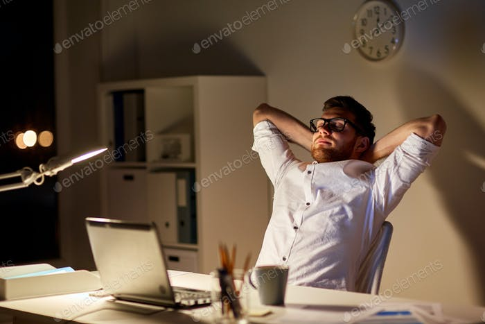 man with laptop stretching at night office