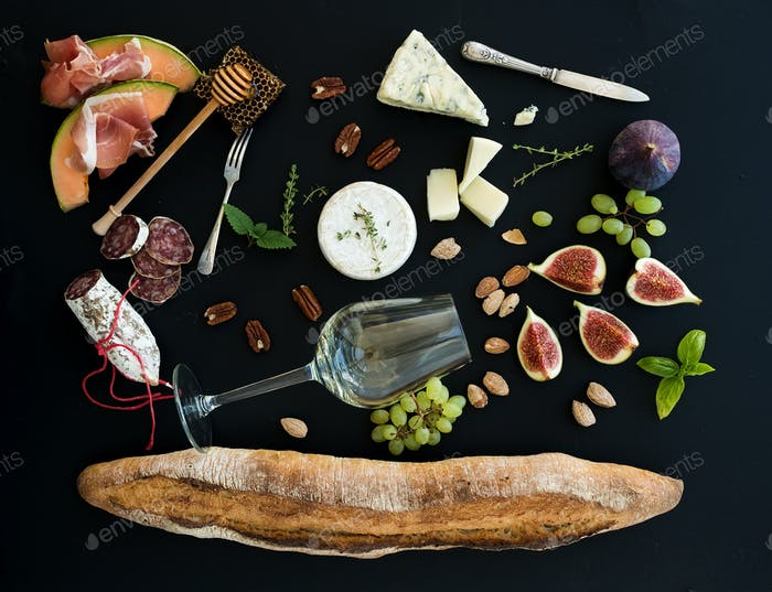 Baguette, glass of white, figs, grapes, nuts, cheese variety, meat appetizers, herbs