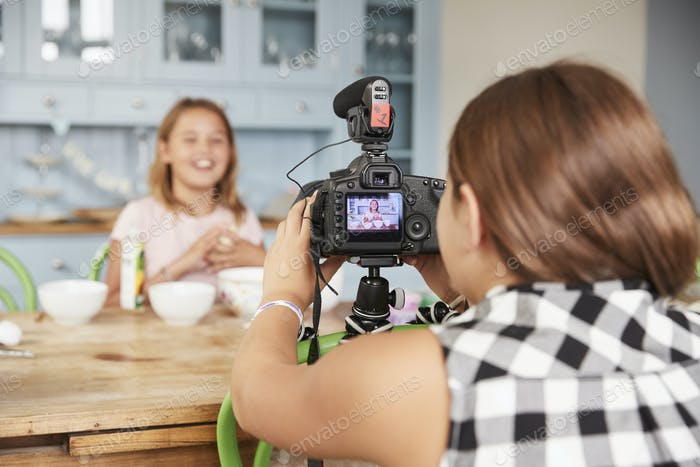 Girl filming her friend for cookery video blog in kitchen