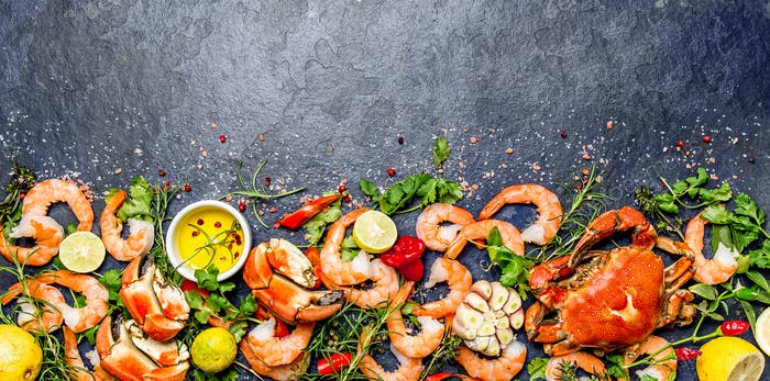 Fresh raw seafood - shrimps and crabs with herbs and spices on dark gray background