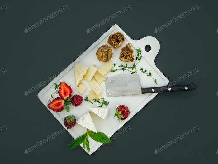 Cheese and fruit set on a dark surface