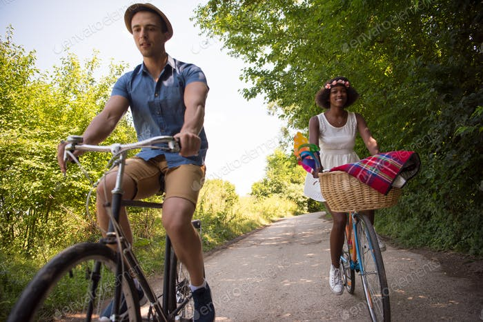 Young multiethnic couple having a bike ride in nature