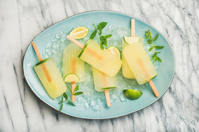 Summer lemonade popsicles with lime, mint leaves and chipped ice
