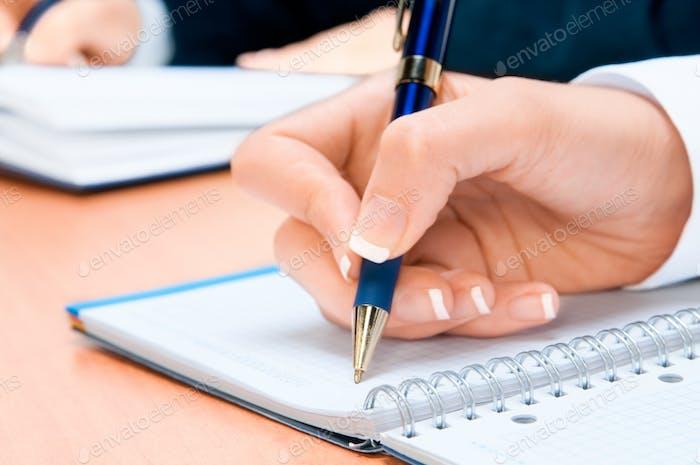 Abgeschnittenes Bild der Hand der jungen Frau Notizen