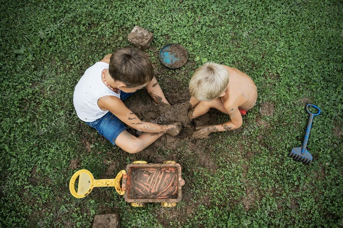 Top view of two brothers sitting on  grass playing with mud