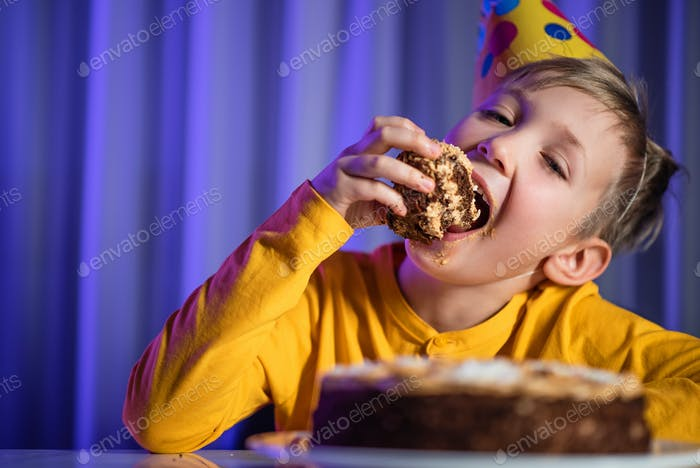 Happy child takes a piece of celebration cake and then bite it.