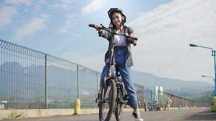 Young Asian woman break  ride bicycle  before go to work