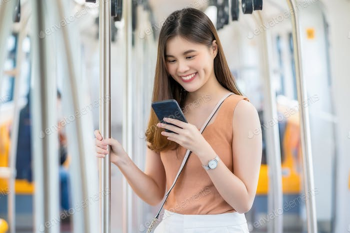 Young Asian woman passenger using smart mobile phone and looking to outside of subway train