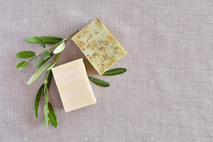 Handmade soap bars and olive branches on gunny background. Top v